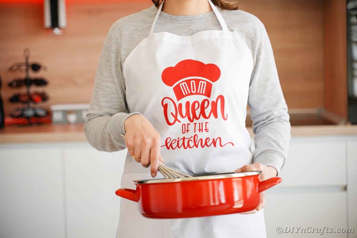 Woman holding red skillet in white and red mothers day apron