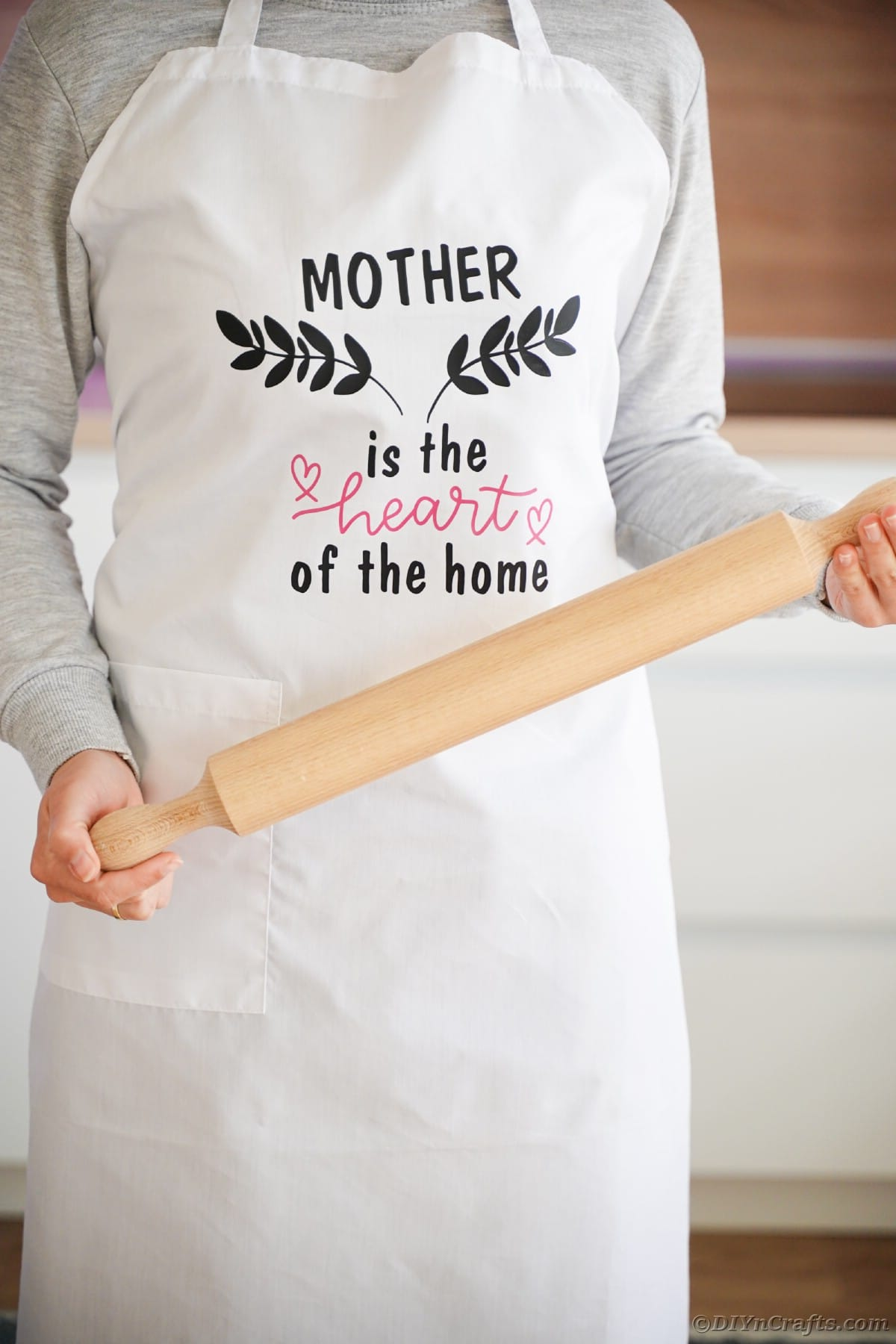 Woman with black vinyl message on front of apron holding rolling pin