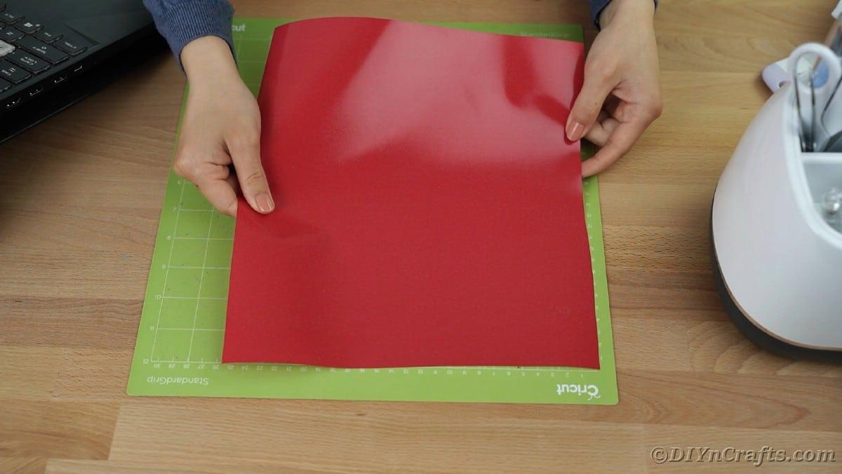 Placing red vinyl on green Cricut mat