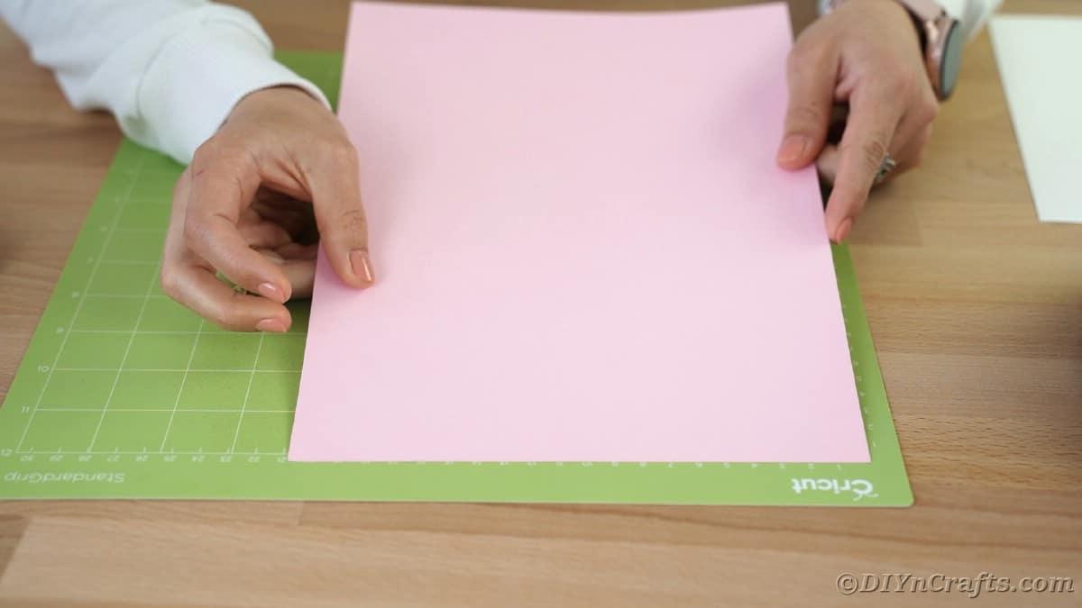 Loading pink paper onto Cricut mat