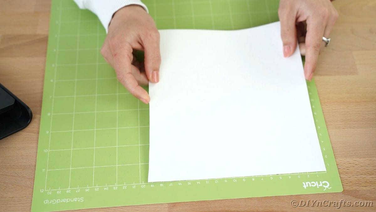 Placing green paper onto Cricut mat