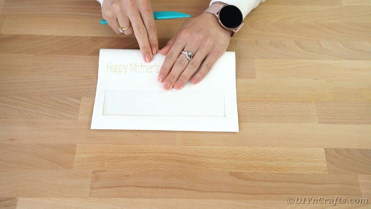 Folding white card in half