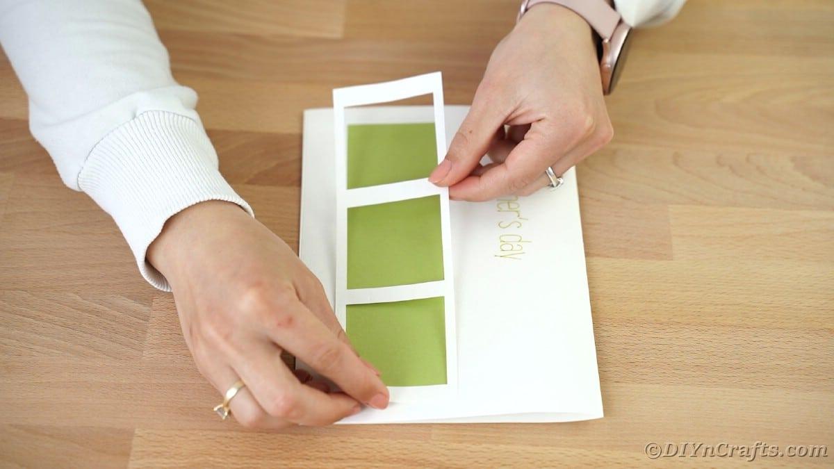 Gluing white frame over green shape on card