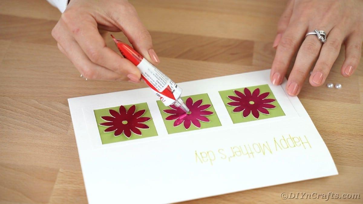 Gluing dark pink flowers onto white card