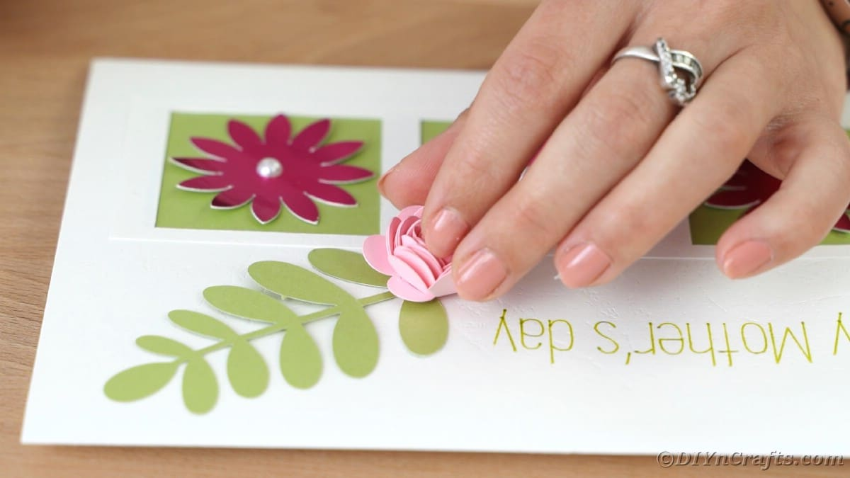 Placing pink flower on green leaf of card