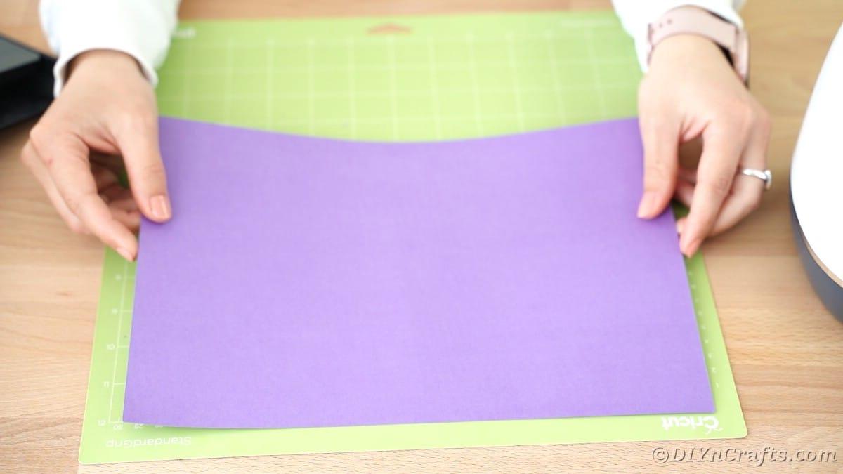 Placing purple paper on Cricut mat