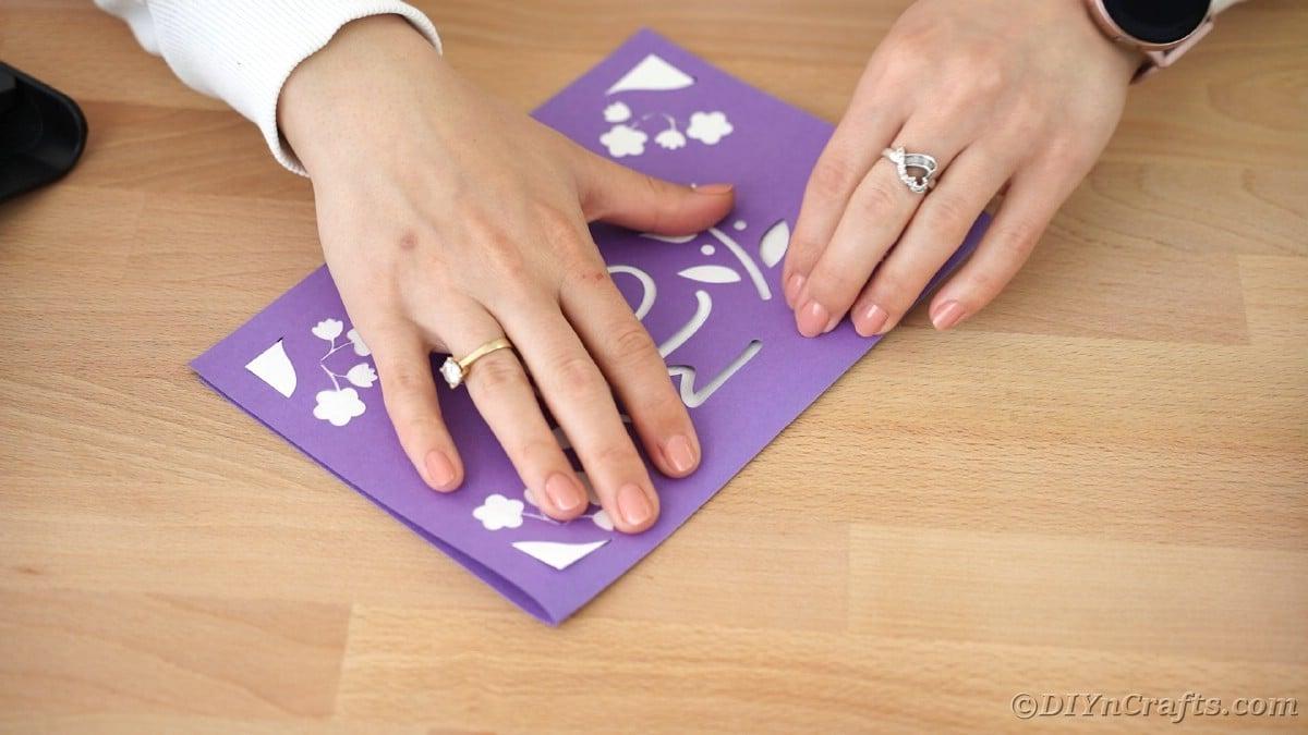 Folding purple card in half