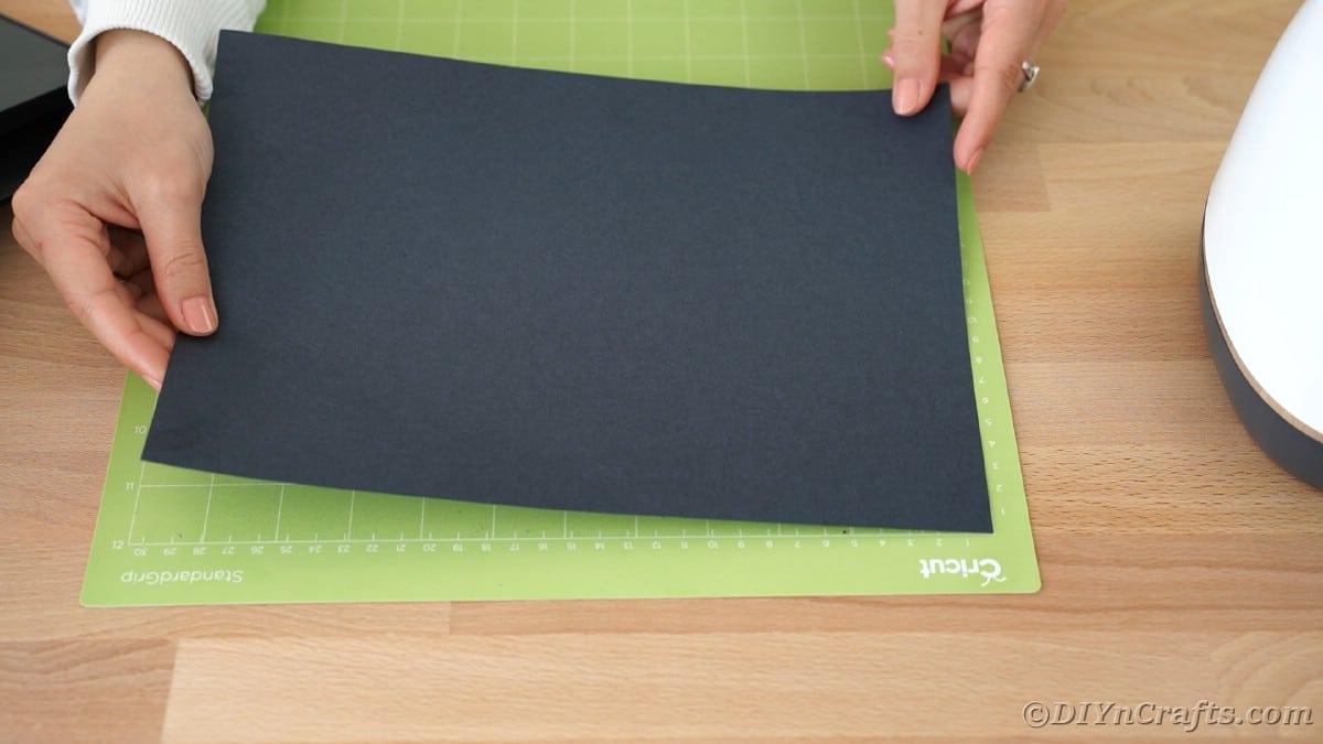 Placing black paper onto Cricut mat