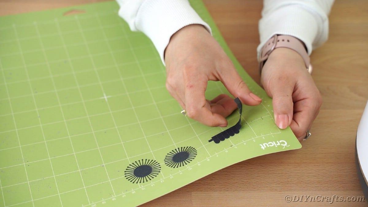 Peeling black paper off of Cricut mat