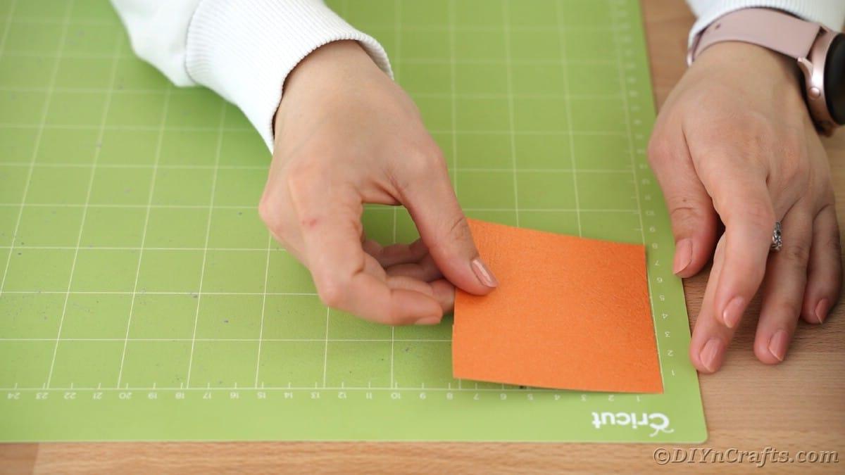 Placing orange paper on cricut mat