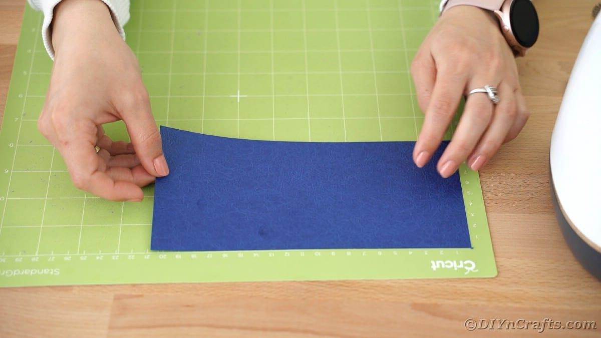 Placing blue paper onto Cricut mat