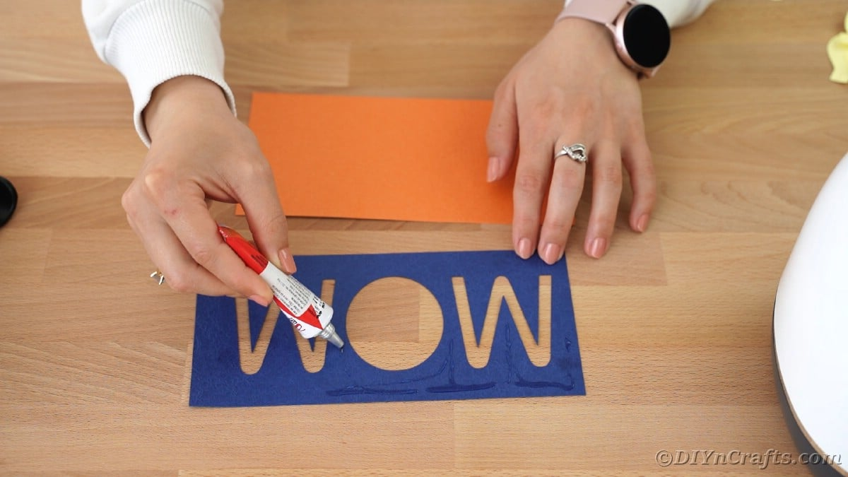 Adding glue to blue paper that says mom
