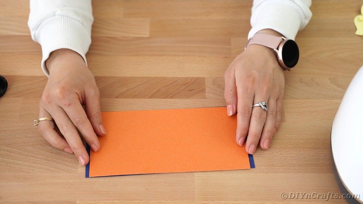 Gluing orange paper onto blue mom paper