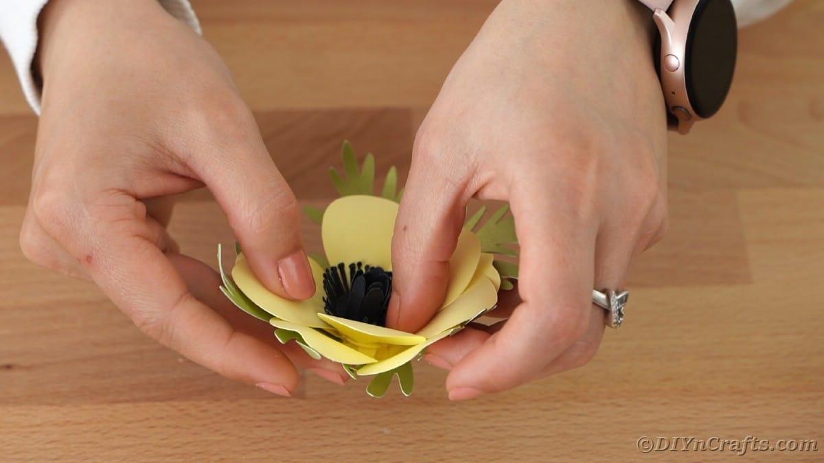 Gluing black flower in center of yellow flower