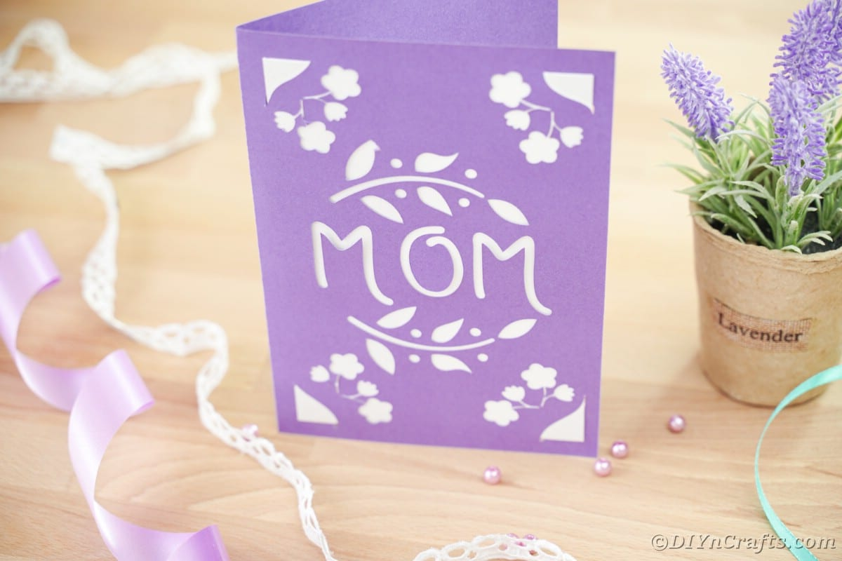 Purple mothers day card sitting on table by potted plant