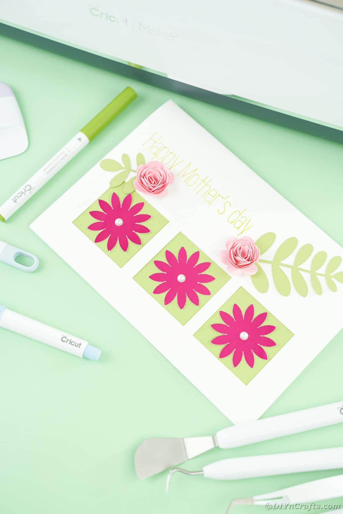 White card with pink flowers on green table by cricut tools
