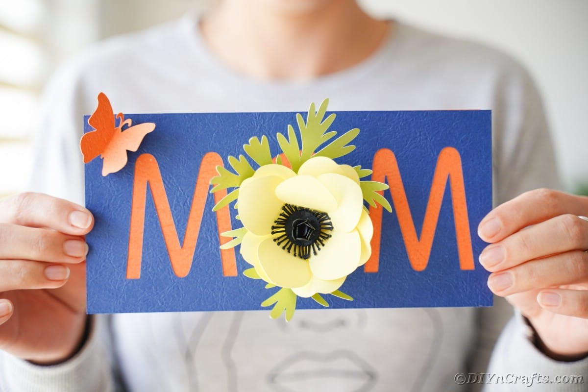 Woman holding blue card with mom and flowers