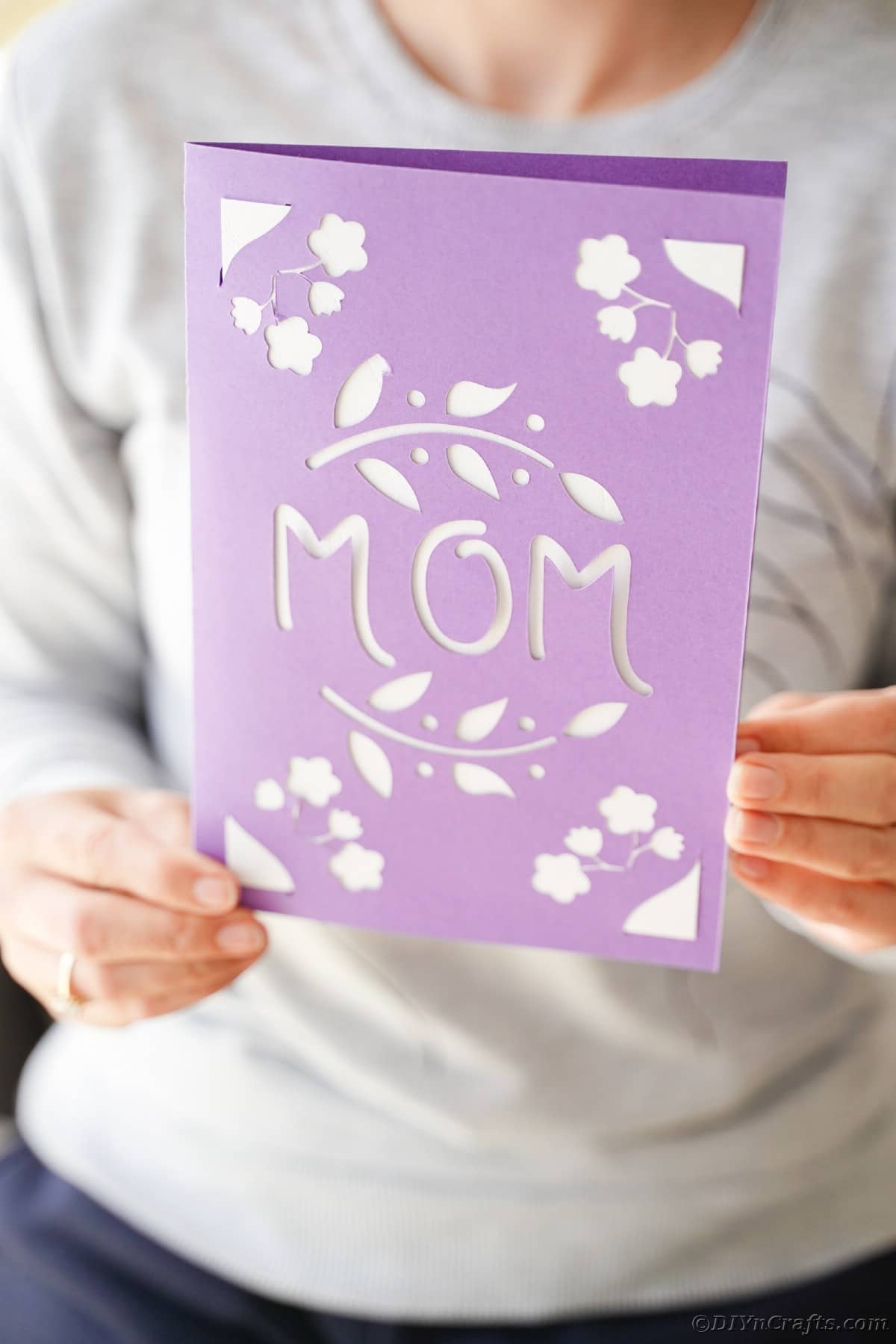 Woman holding purple mothers day card