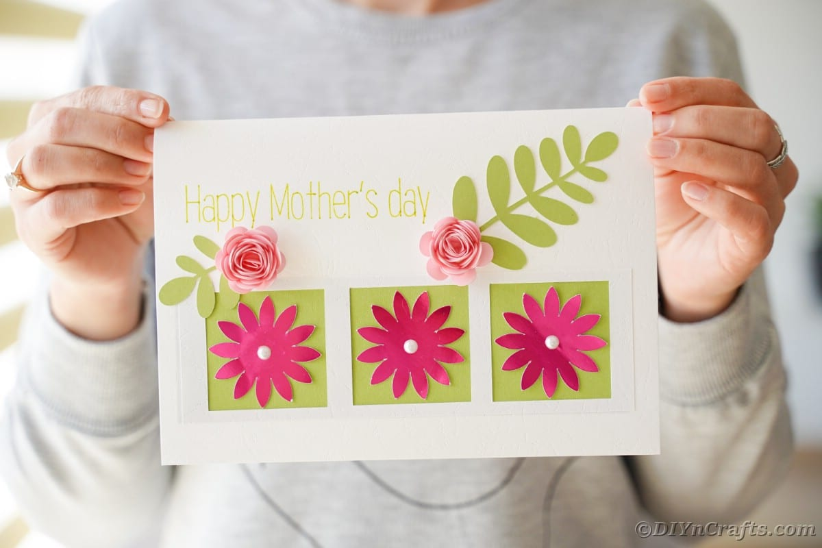 Mothers day card with pink flowers and green leaves