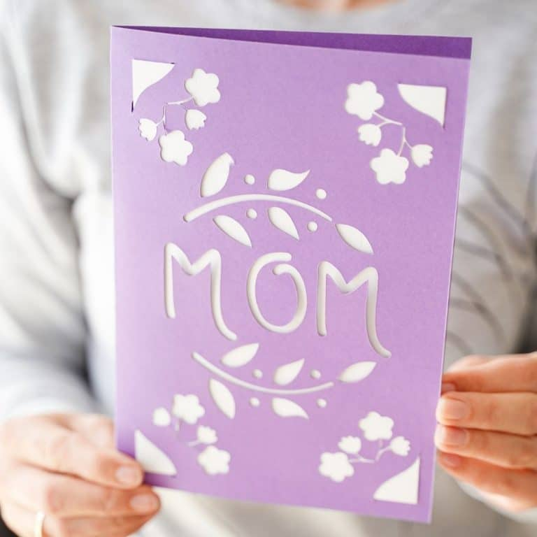 Woman holding purple card that says mom