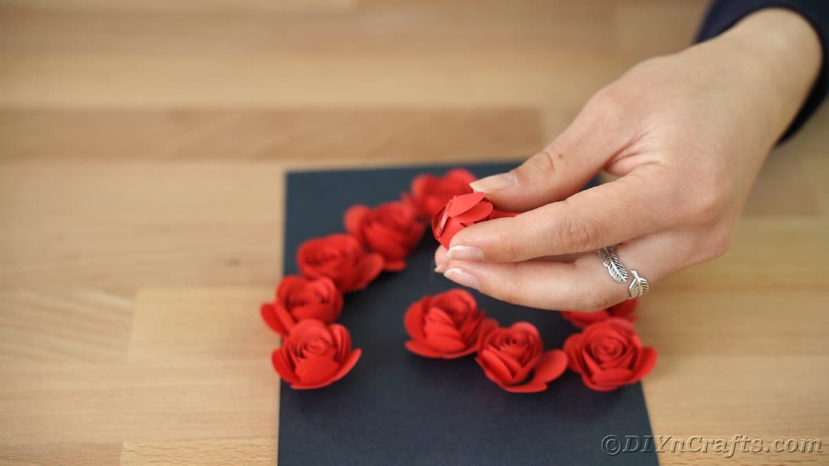 Gluing red flowers onto black cardboard