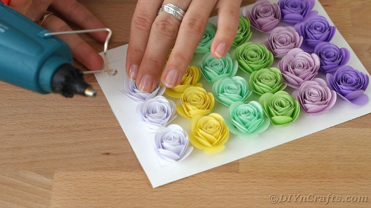 Gluing paper flowers onto frame backing