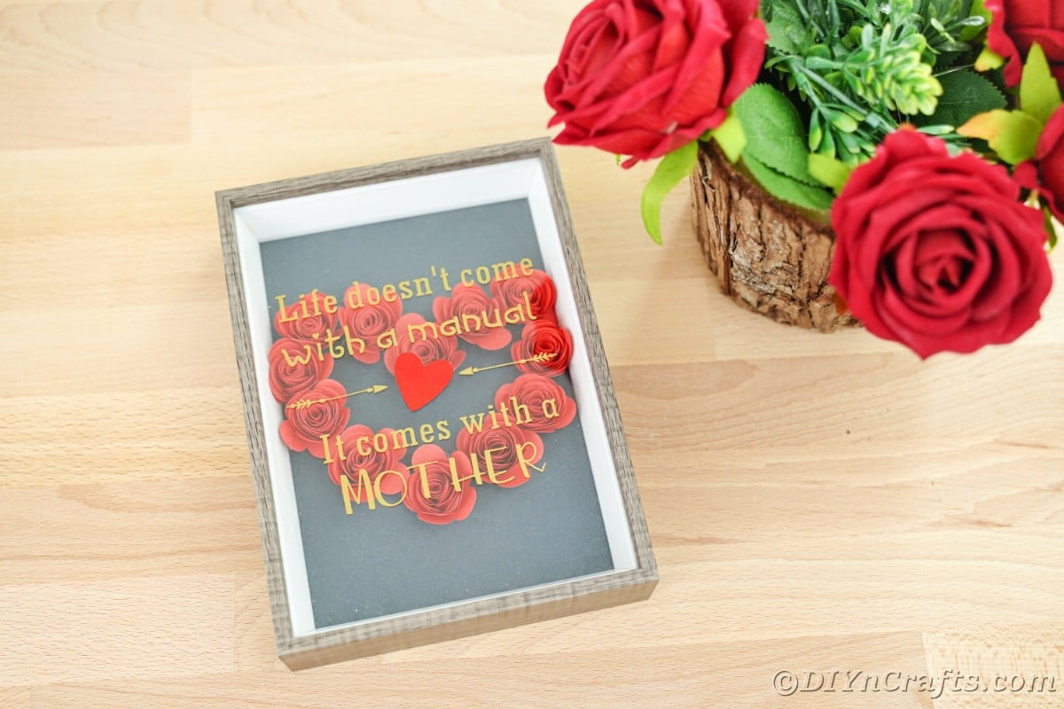 Red flower heart in frame on wood table