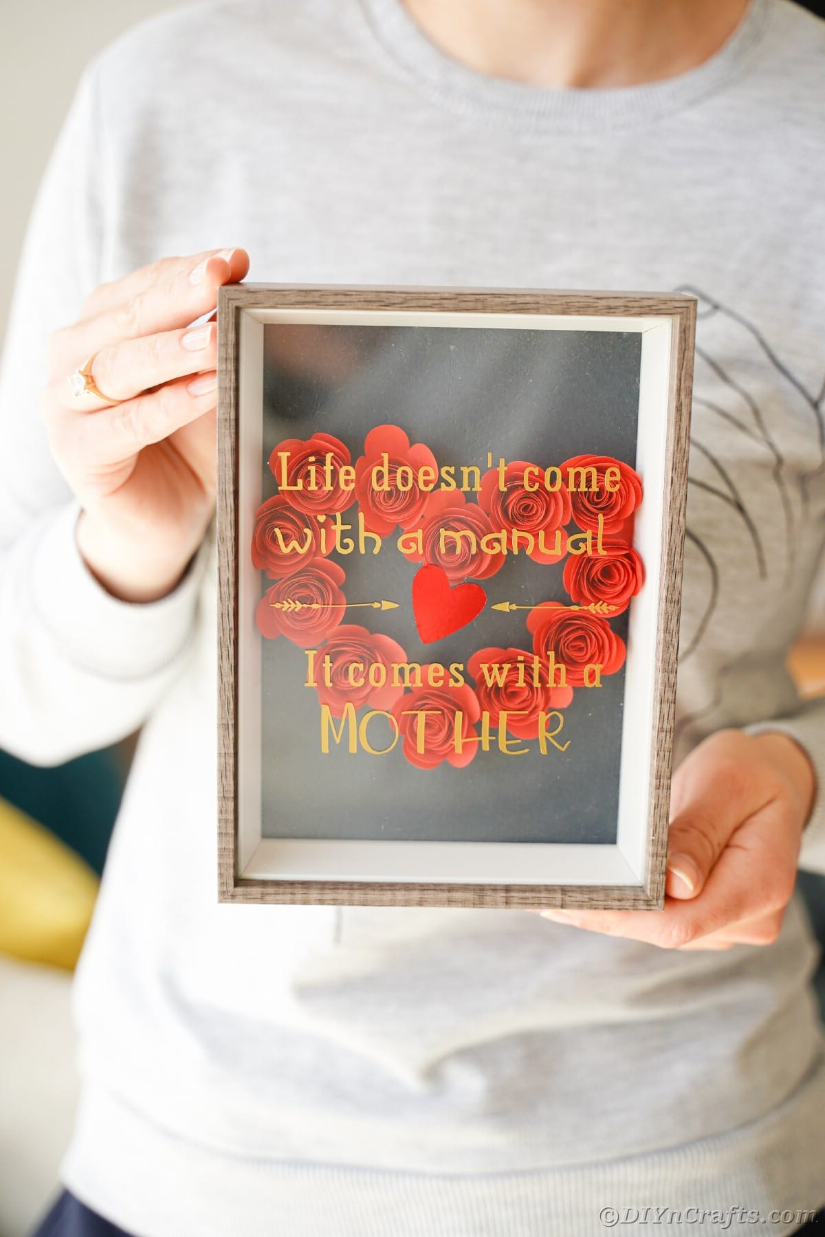 Woman holding framed mothers day message with red flower heart