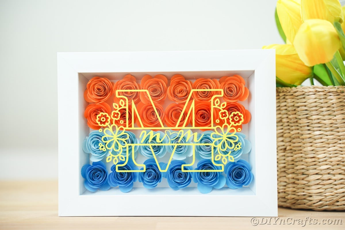 White mother's day shadowbox next to wicker basket