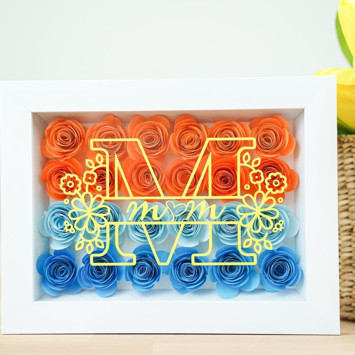 White shadowbox with colorful flowers on table