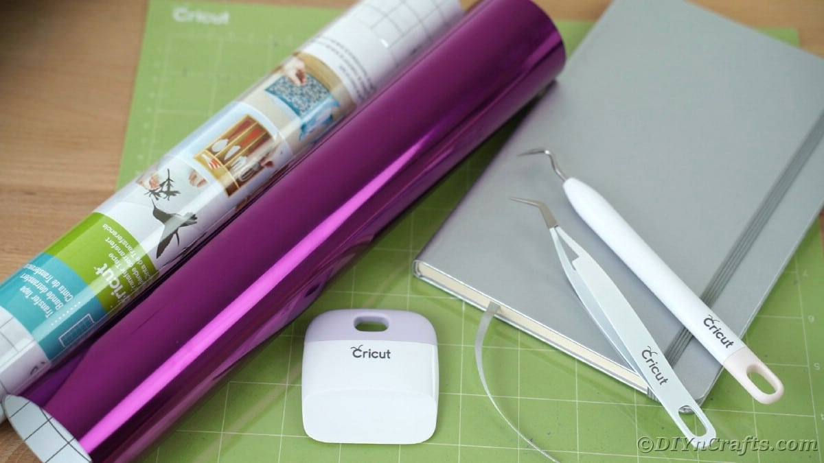 Purple foil roll on top of Cricut mat by gray journal
