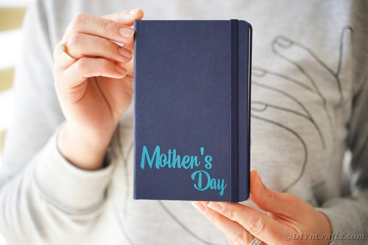 Woman holding blue journal with mother's day on bottom corner