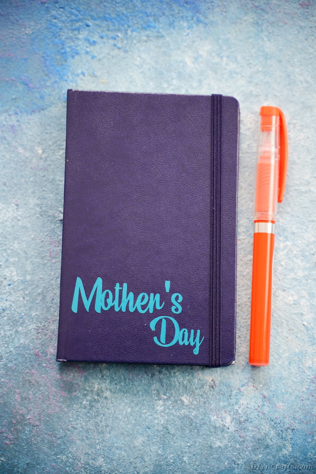 Dark blue journal with light blue mothers day printed on bottom corner next to orange pen