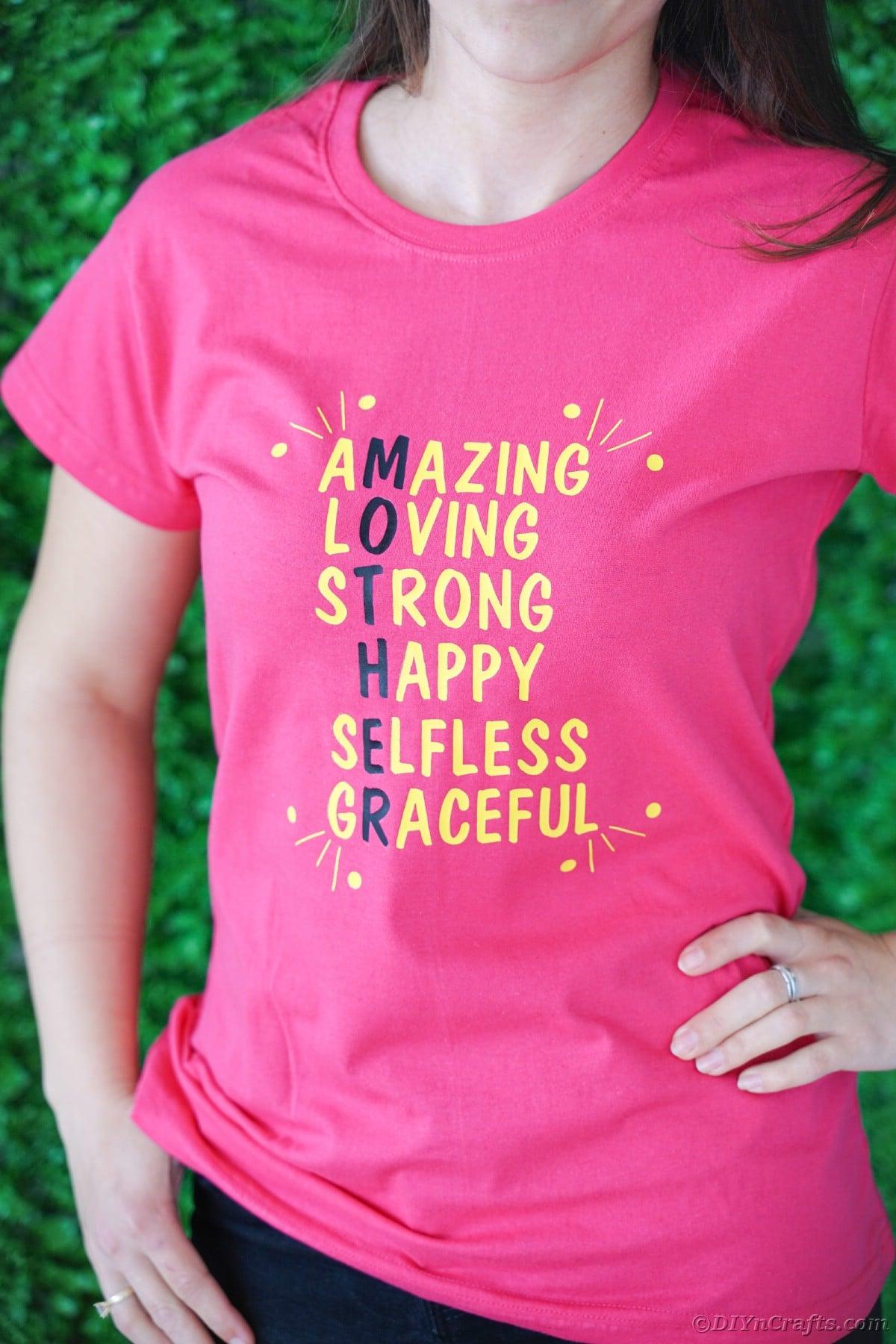 Pink t-shirt on woman agianst green shrub