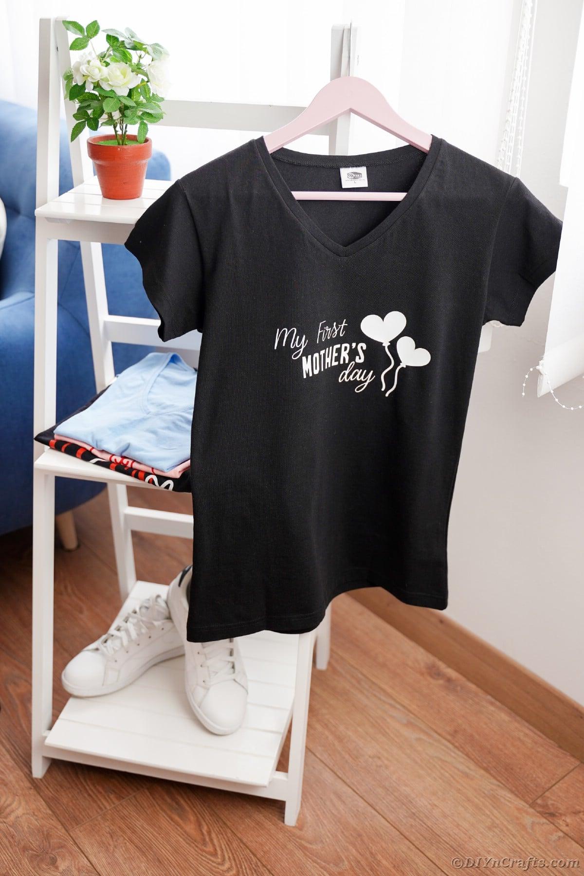 Black tshirt hanging on white shelf