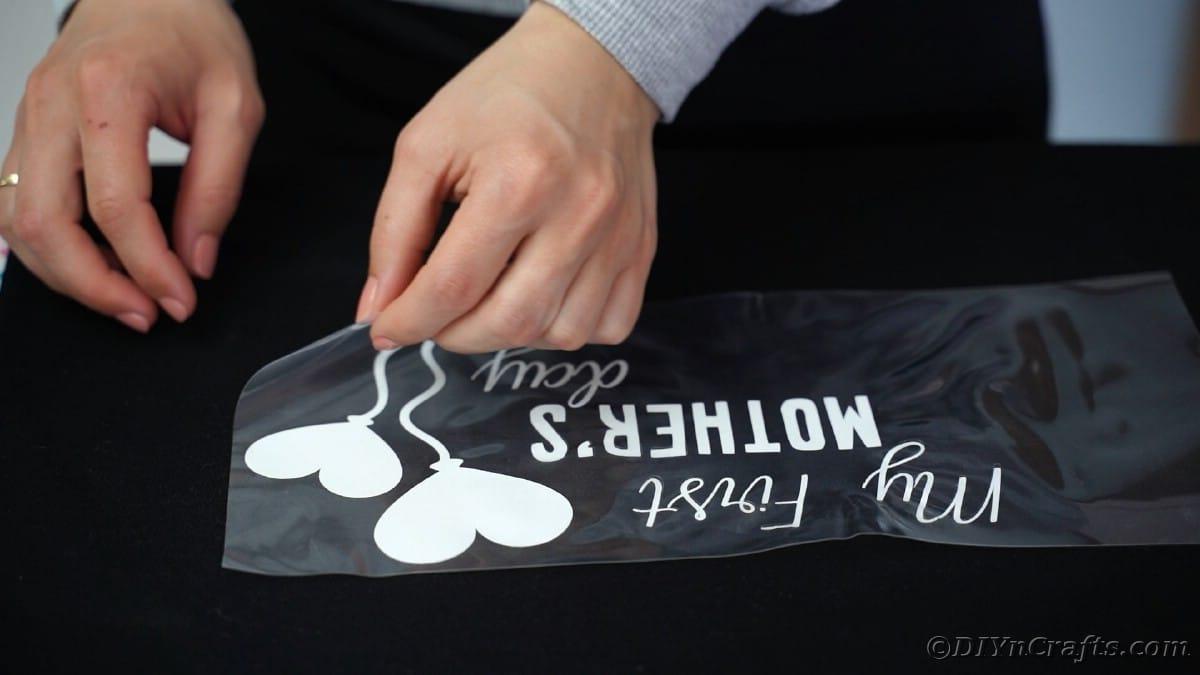 Peeling carrier sheet off top of black tshirt