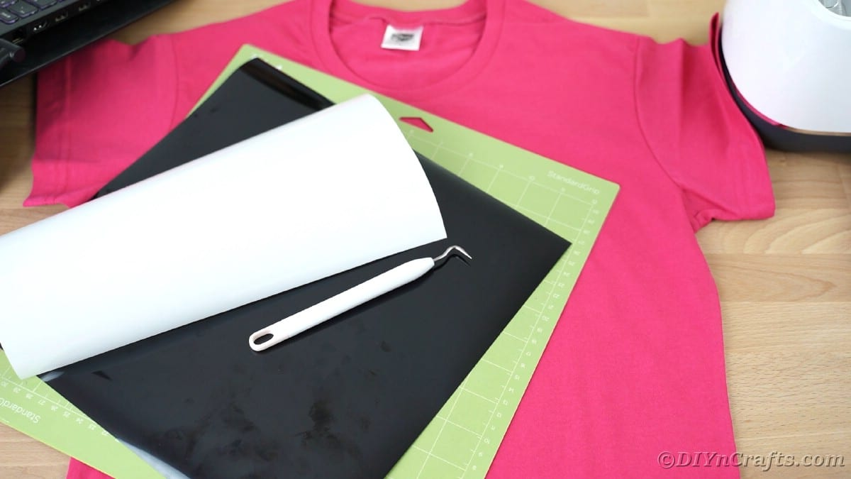 Pink tshirt with Cricut mat and vinyl on top