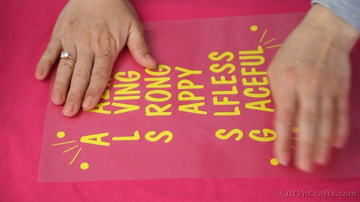 Placing vinyl letters onto pink tshirt