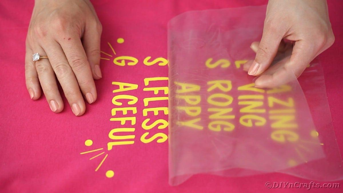 Peeling carrier sheet off of vinyl on tshirt