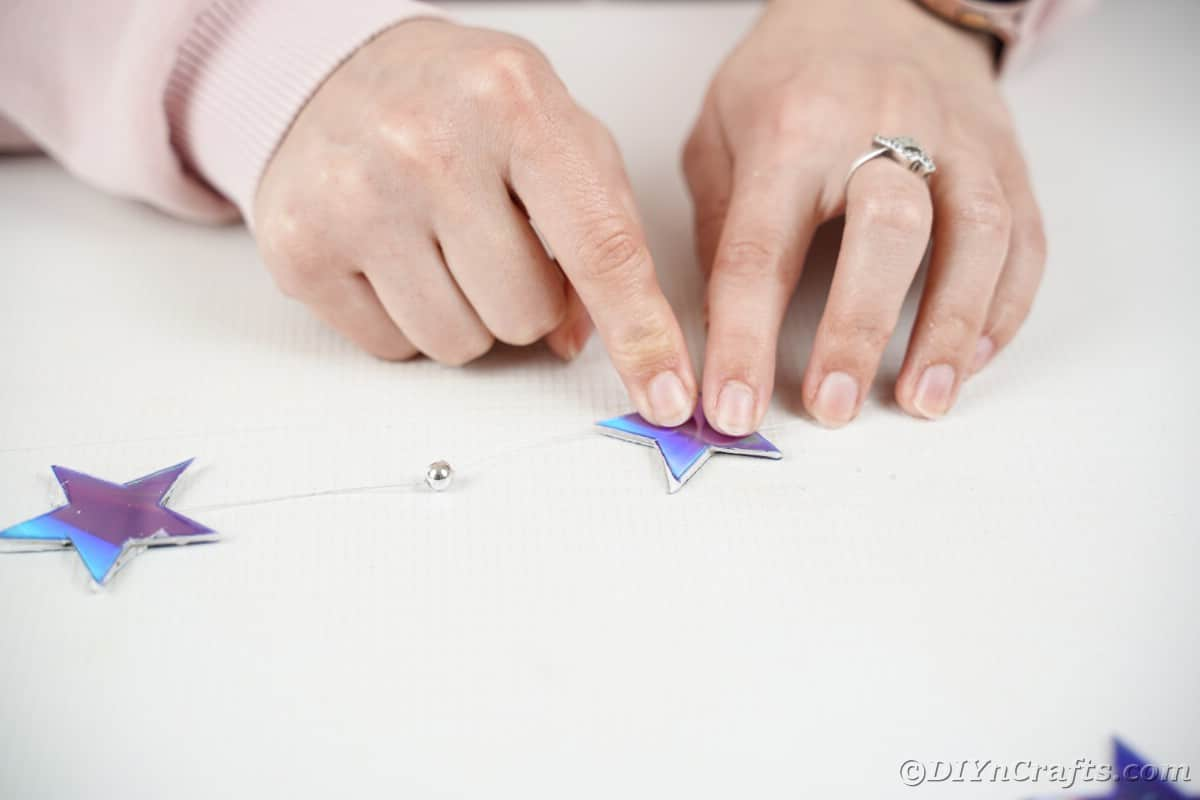 Hand pushing star down onto table
