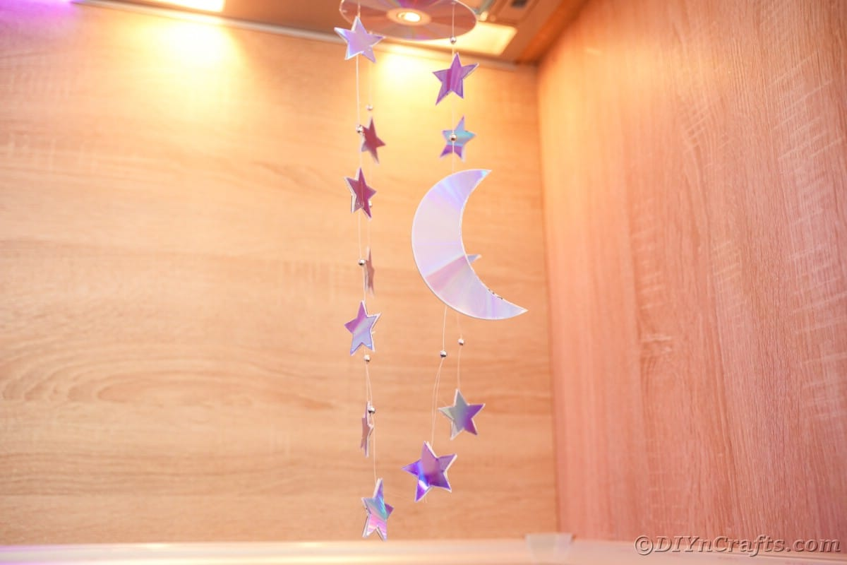 Stars and moon mobile hanging under light in kitchen