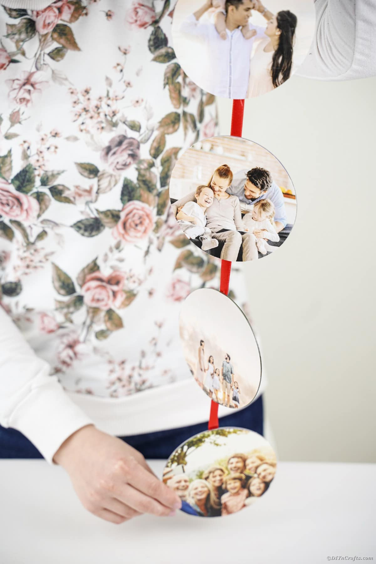 Woman in floral shirt holding craft picture ribbon above white table