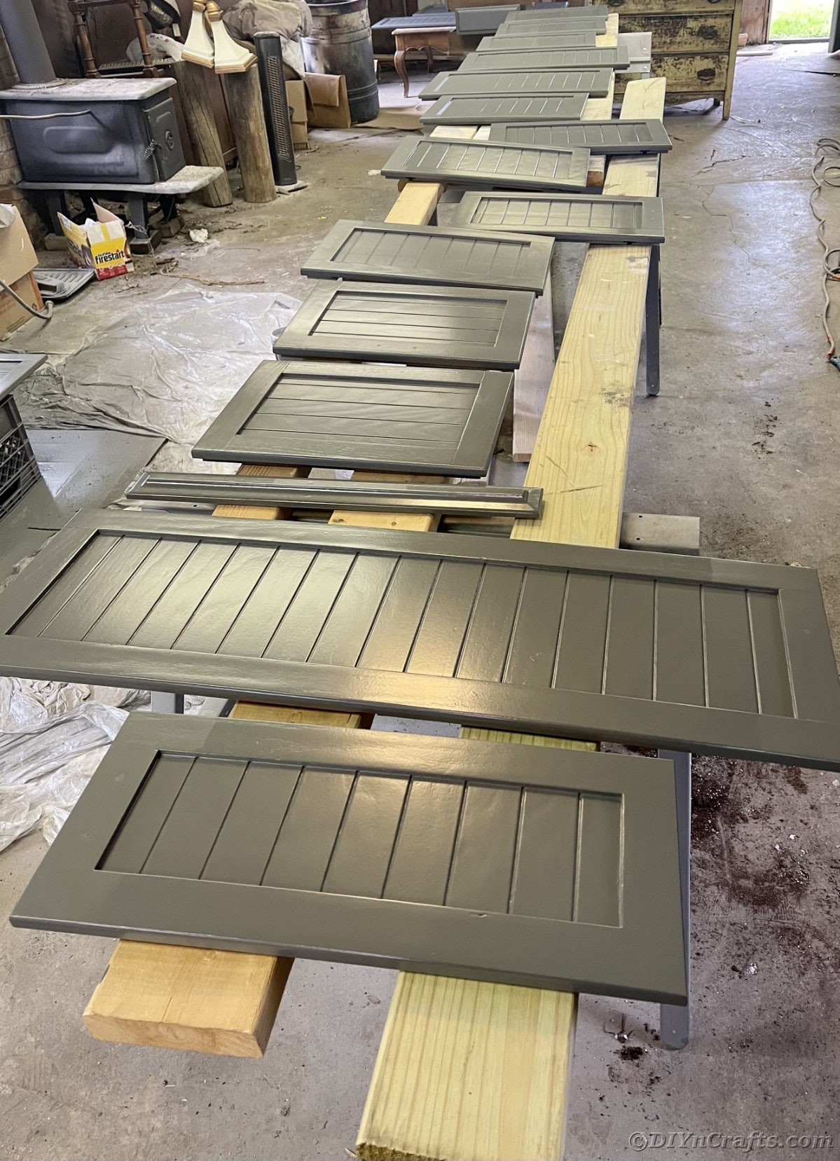 Gray shutter door cabinets laying on top of 2x4s