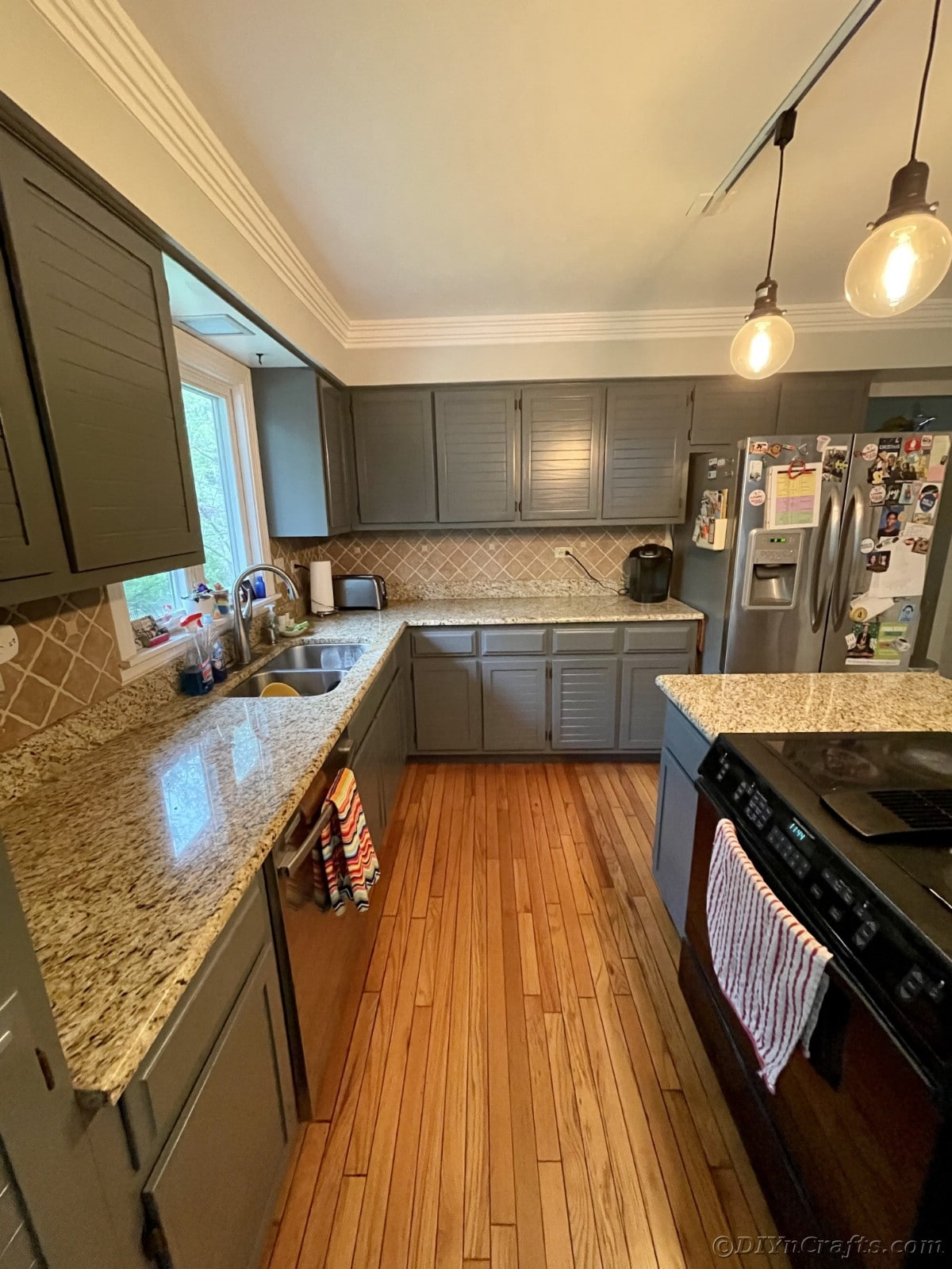 Kitchen with black stove and gray cabinets