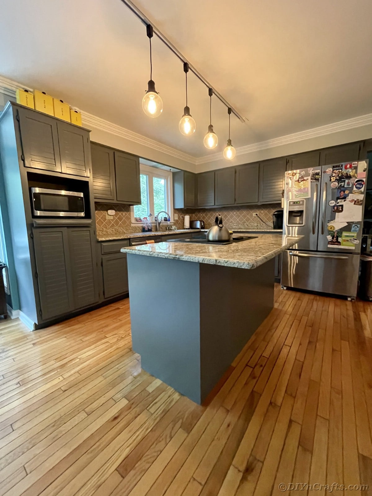 Kitchen with gray cabinets and dangling lights over island