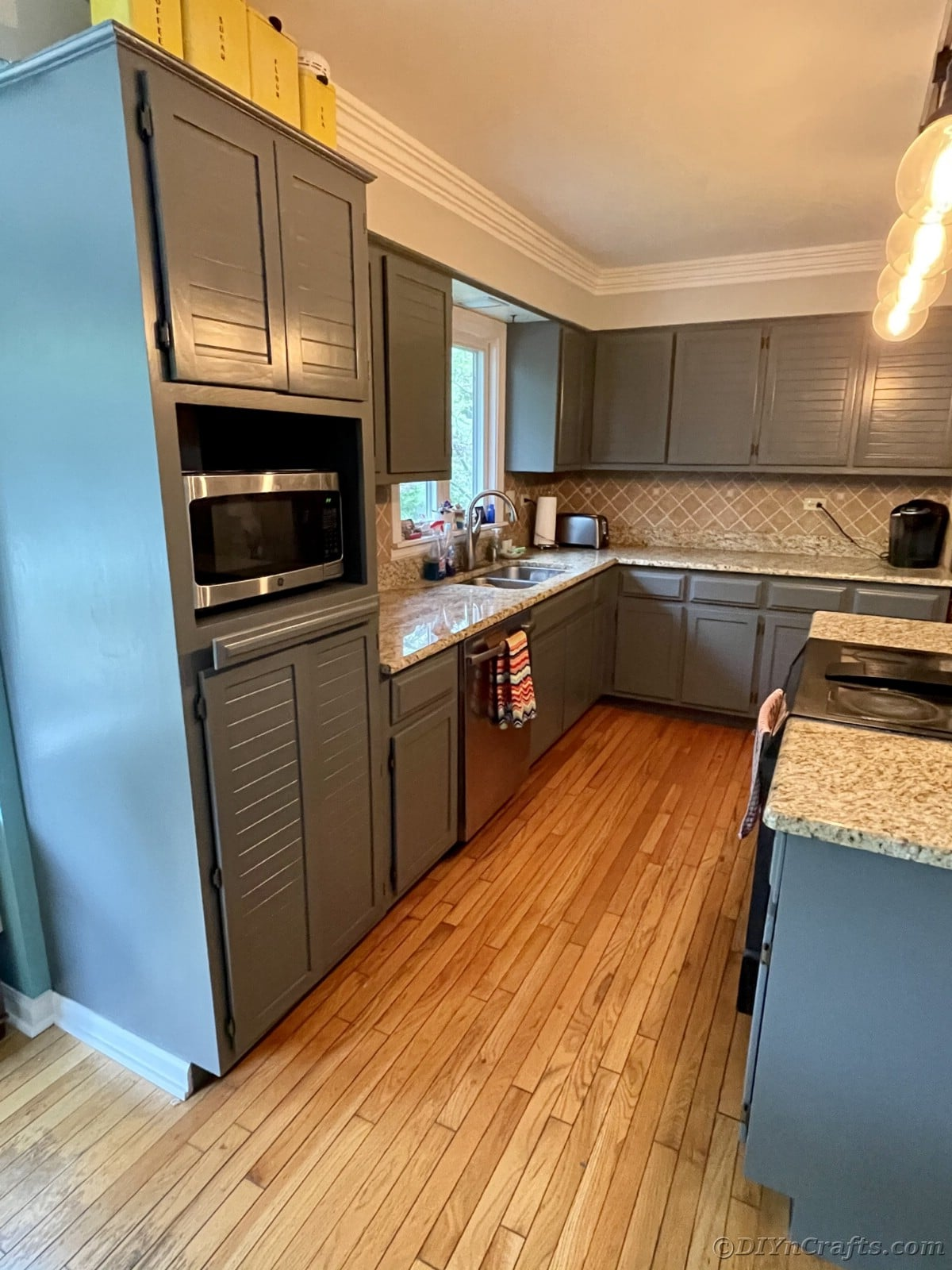 Kitchen with gray cabinets and marbled countertops