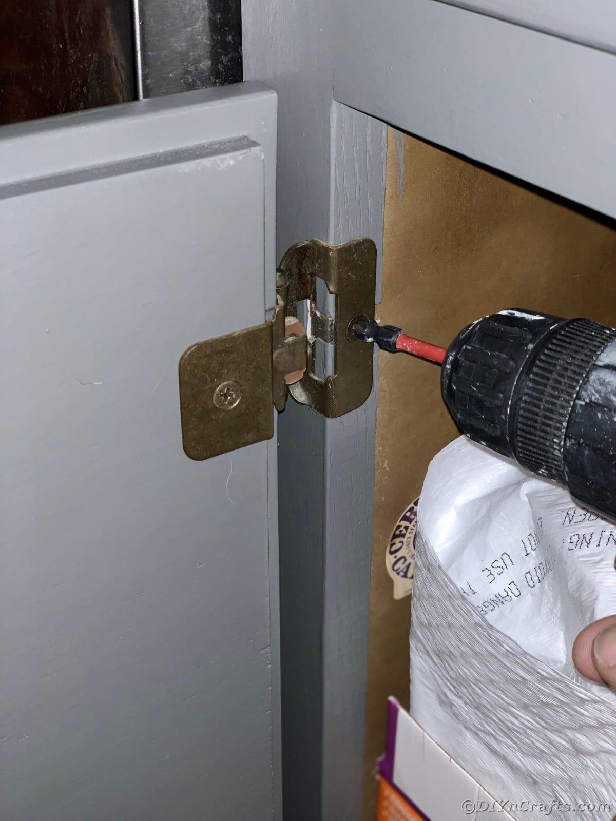 Screwing hardware back onto cabinet door