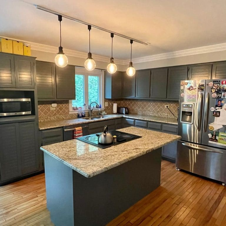 Renovated kitchen with gray cabinets and marbled counters on island