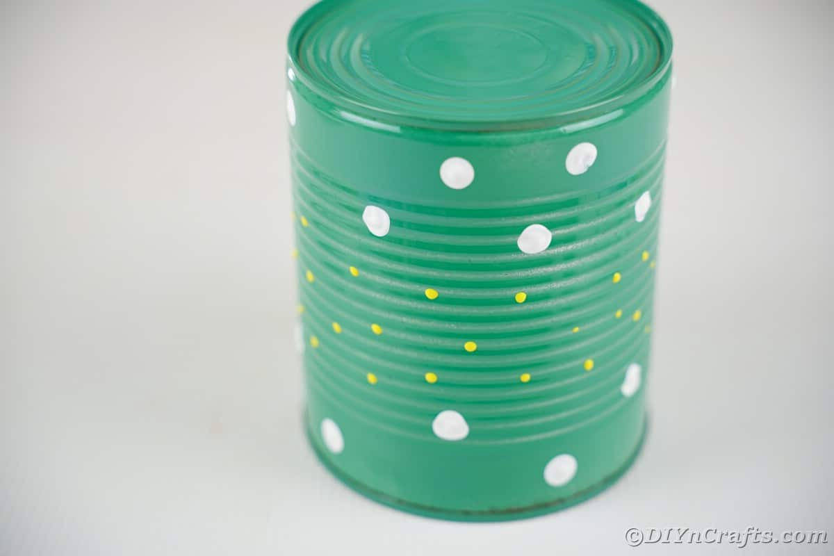 Green tin can with white and yellow dots