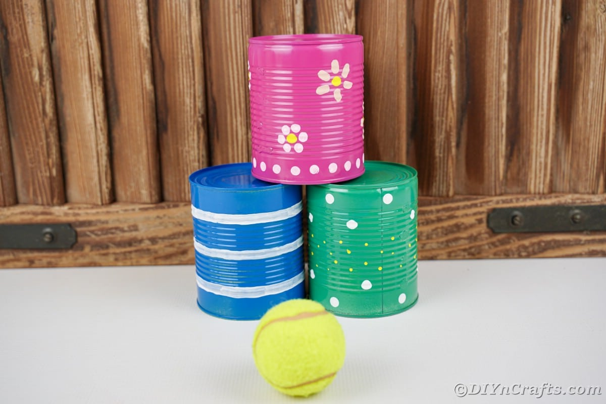 Blue green and pink tin cans with tennis ball in front of wood paneling